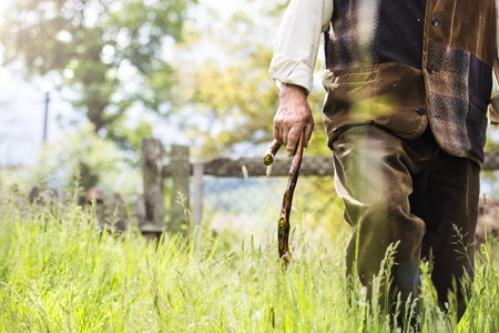 Close-up of old farmer with beard and hat is walking in his back yard