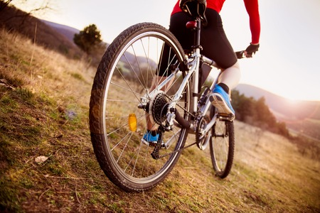 Photo pour Detail of cyclist man feet riding mountain bike on outdoor trail in sunny meadow - image libre de droit