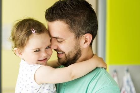 Photo pour Indoor portrait of young father hugging his little daughter - image libre de droit