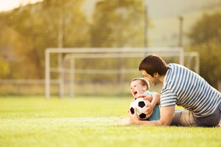 Photo pour Young father with his little son playing football on football pitch - image libre de droit