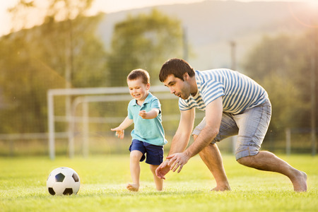 Foto de Young father with his little son playing football on football pitch - Imagen libre de derechos