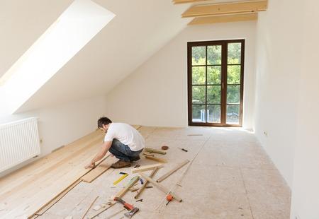 Photo pour Handyman installing wooden floor in new house - image libre de droit