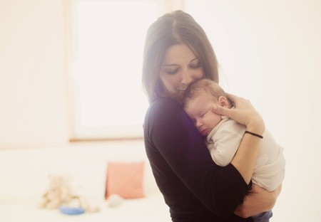 Photo pour Young mother is holding her little baby - image libre de droit