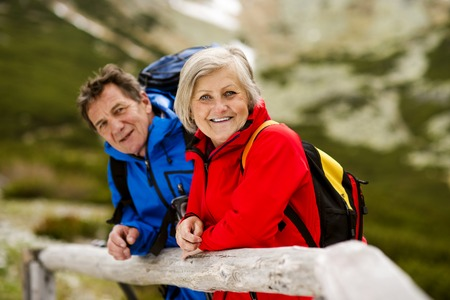 Photo for Senior tourist couple hiking at the beautiful mountains - Royalty Free Image