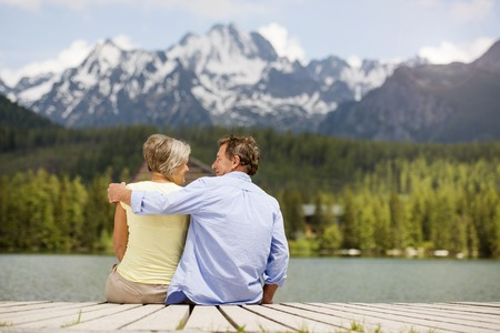 Foto de Senior couple sitting on pier above the mountain lake with mountains in background - Imagen libre de derechos