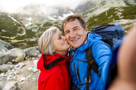 Foto de Senior tourist couple hiking and taking selfie at the beautiful mountains - Imagen libre de derechos