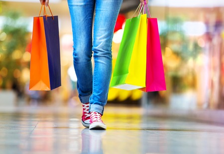 Photo pour Shopping time, closeup of teenage girl legs with shopping bags at shopping mall - image libre de droit