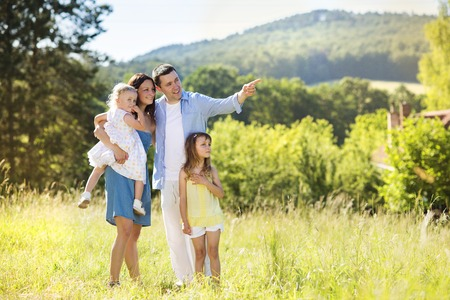 Photo for Portrait of young happy ypung family walking in sunny meadow - Royalty Free Image