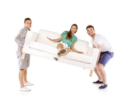 Photo for Two young handsome men lifting sofa with young beautiful woman sitting on it, isolated on white background - Royalty Free Image