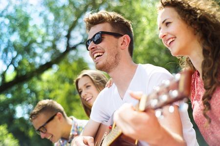 Photo pour Group of happy friends with guitar having fun outdoor - image libre de droit