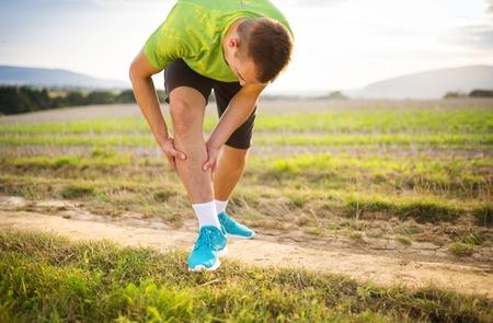 Foto de Runner leg and muscle pain during running training outdoors in summer nature - Imagen libre de derechos