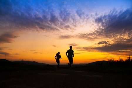 Photo for Silhouette of young couple running in sunset - Royalty Free Image