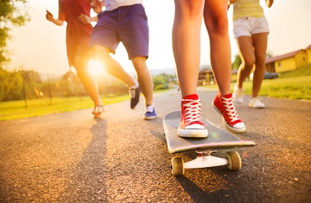 Photo pour Closeup of legs and sneakers of young people on skateboard - image libre de droit