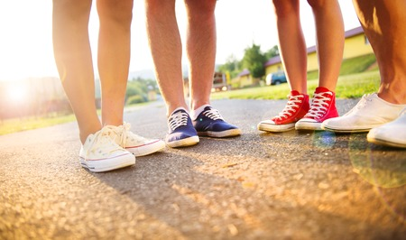Photo pour Legs and sneakers of teenage boys and girls standing on the sidewalk - image libre de droit
