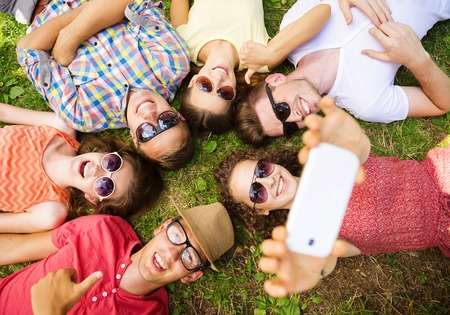 Foto de Group of young people having fun in park, lying on the grass and taking selfie - Imagen libre de derechos