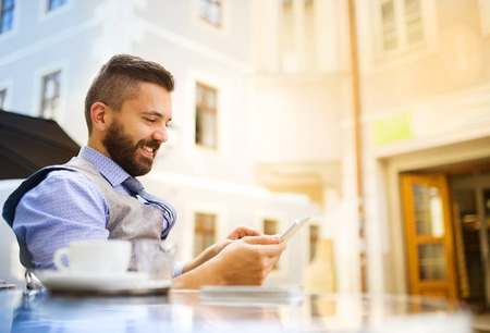 Photo pour Modern hipster businessman drinking espresso coffee in the city cafe during lunch time and using mobile phone - image libre de droit