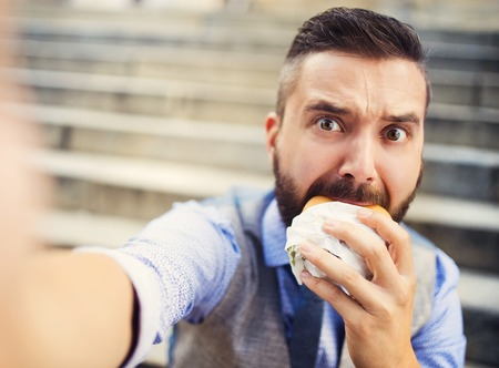 Photo pour Modern hipster businessman having lunch break, sitting on stairs in town center and eating burger - image libre de droit