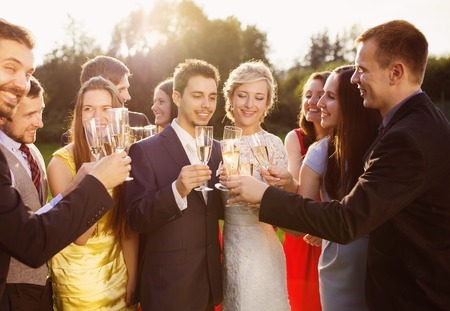 Photo for Wedding guests clinking glasses with the newlyweds at the wedding reception outside - Royalty Free Image