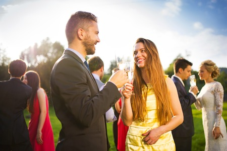 Photo for Wedding guests clinking glasses at the wedding reception outside - Royalty Free Image