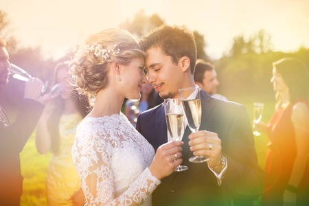 Photo pour Young newlyweds clinking glasses and enjoying romantic moment together at wedding reception outside - image libre de droit