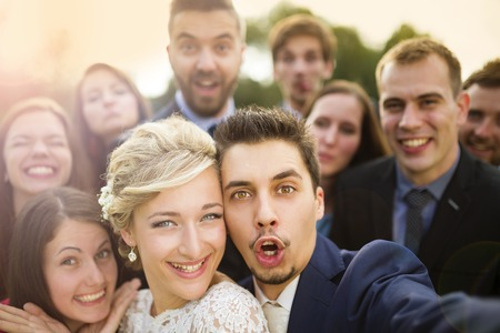 Foto de Young couple of newlyweds with group of their firends taking selfie and making funny grimaces - Imagen libre de derechos