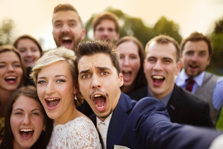 Photo for Young couple of newlyweds with group of their firends taking selfie and making funny grimaces - Royalty Free Image