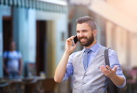 Photo pour Handsome hipster modern businessman with beard walking in town and calling on mobile phone - image libre de droit