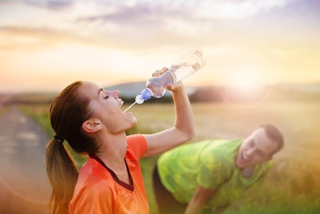 Photo pour Cross-country trail running couple having water break at sunset - image libre de droit
