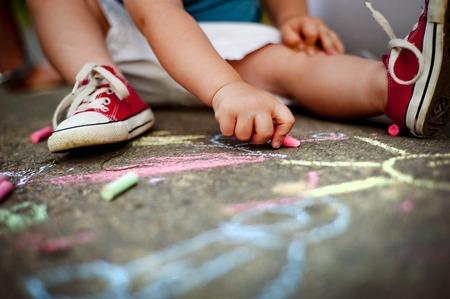 Foto de Close up of little boy in canvas shoes drawing with chalks on the sidewalk - Imagen libre de derechos