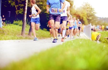 Photo pour Group of unidentified marathon racers running, detail on legs - image libre de droit