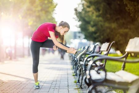 Foto de Young female runner is jogging in the city on a quay. Sport lifestyle. - Imagen libre de derechos