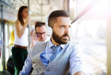 Photo for Handsome hipster modern man with headphones traveling by tram in town - Royalty Free Image