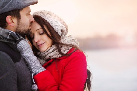 Photo pour Young couple hugging by the river in winter weather - image libre de droit