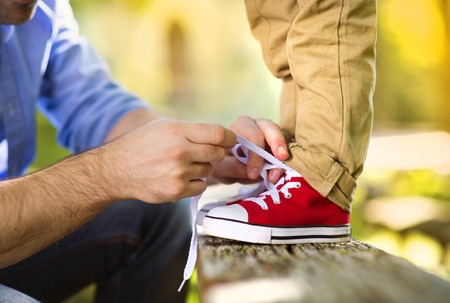 Photo for Father is helping his son to tie his shoes in summer nature - Royalty Free Image