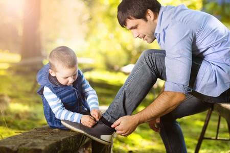 Photo pour Father and son spending time together in summer nature, little boy is tying his father\'s shoes - image libre de droit