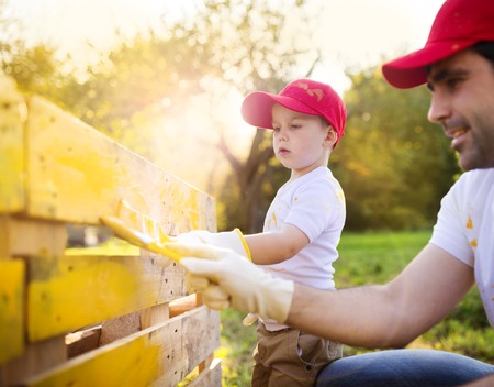 Photo for Cute little boy and his father in red caps painting wooden fence together on sunny day in nature - Royalty Free Image