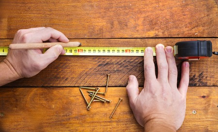 Photo pour Close up of male hand measuring and marking wood flooring with tape measure - image libre de droit