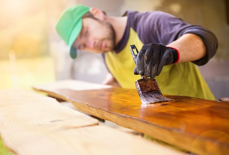 Photo for Handyman varnishing pine wooden planks in patio outside the new house - Royalty Free Image