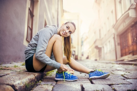 Photo pour Young female runner is tying her running shoes on tiled pavement in old city center - image libre de droit