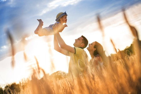 Photo for Happy pregnant family with little daughter spending time together in sunny field - Royalty Free Image