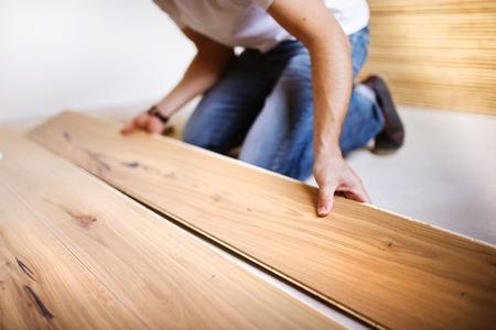Photo pour Unrecognizable handyman installing wooden floor in new house - image libre de droit