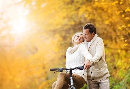 Photo pour Active senior couple together enjoying romantic walk with bicycle in golden autumn park - image libre de droit