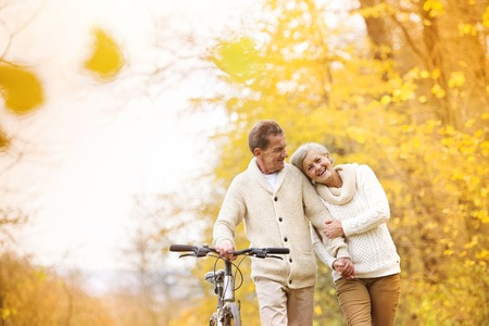 Foto de Active senior couple together enjoying romantic walk with bicycle in golden autumn park - Imagen libre de derechos