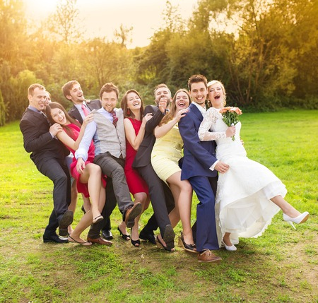 Photo pour Full length portrait of newlywed couple having fun with bridesmaids and groomsmen in green sunny park - image libre de droit