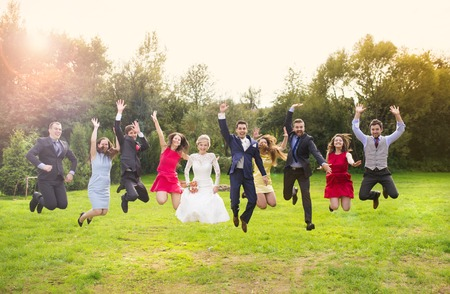 Photo for Full length portrait of newlywed couple with bridesmaids and groomsmen jumping in green sunny park - Royalty Free Image