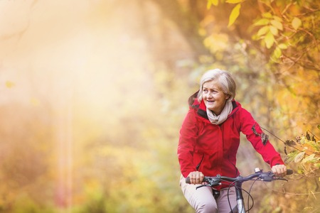 Photo pour Active senior woman ridding bike in autumn nature. - image libre de droit