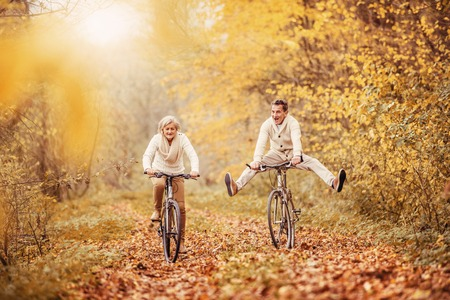 Foto de Active seniors ridding bike in autumn nature. They having fun outdoor. - Imagen libre de derechos