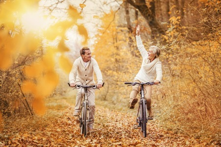 Photo pour Active seniors ridding bike in autumn nature. They having fun outdoor. - image libre de droit