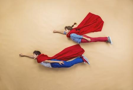 Foto de Children are playing as superheroes with red coats - Imagen libre de derechos