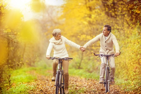 Foto de Active seniors riding bike in autumn nature. They relax outdoor. - Imagen libre de derechos